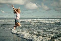 Petite fille sautant sur la plage au bord de mer bleu Photographie stock