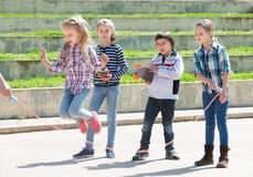 Petite fille sautant tandis que jeu de corde de saut Photographie stock libre de droits