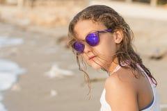 Petite fille se baignant sur la plage avec des verres Image stock
