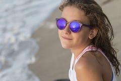 Petite fille se baignant sur la plage avec des verres Image libre de droits