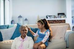 Petite-fille se brossant les cheveux de grands-mères dans le salon Image libre de droits