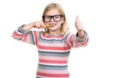 Petite fille se brossant les dents d'isolement sur le fond blanc Photographie stock libre de droits