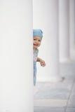 Petite fille se cachant dans les colonnes Images stock