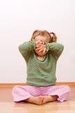 Petite fille se cachant derrière ses mains - copyspace Photo stock