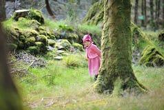 Petite fille se cachant derrière un arbre Photo libre de droits