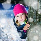 Petite fille se cachant derrière un arbre dans le parc d'hiver Image stock