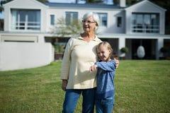 Petite-fille se dirigeant à la distance tandis que grand-mère se tenant près de elle Photographie stock