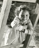 Petite fille se penchant sur l'échelle Photo libre de droits