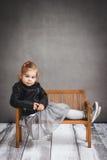 Petite fille se reposant sur un banc en bois Image libre de droits