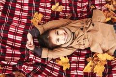 Petite fille se situant dans des feuilles d'érable en parc photographie stock