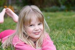 Petite fille se situant dans l'herbe Photographie stock