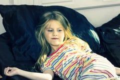 Petite fille se situant dans le lit à la maison photo stock