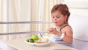 Petite fille se situant dans le lit d'hôpital mangeant son déjeuner banque de vidéos