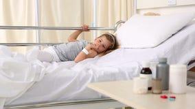 Petite fille se situant dans le lit d'hôpital regardant la médecine banque de vidéos