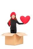 Petite fille se tenant dans la boîte avec un coeur rouge Image libre de droits
