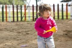 Petite fille se tenant dans le bac à sable Photos stock