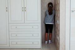 Petite fille se tenant dans le coin photographie stock libre de droits