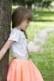 Petite fille se tenant près d'un arbre jugeant son favori bourré Images libres de droits