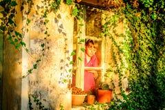 Petite fille se tenant prêt la fenêtre image stock