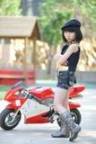 Petite fille se tenant prêt la moto Photos libres de droits