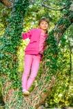 Petite fille se tenant sur l'arbre photos libres de droits