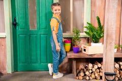 Petite fille se tenant sur le porche avec les pots de fleur colorés et souriant à l'appareil-photo Photo stock