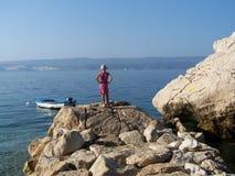 Petite fille se tenant sur les roches observant la mer Photographie stock libre de droits
