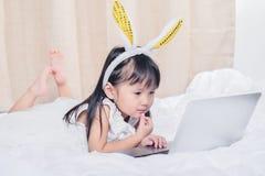 Petite fille se trouvant avec l'ordinateur portable sur le sourire heureux de lit utilisant l'Internet observant et ayant l'amuse image stock
