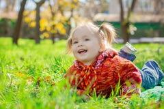 Petite fille se trouvant sur l'herbe en parc images stock
