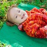 Petite fille se trouvant sur l'herbe en parc photo libre de droits