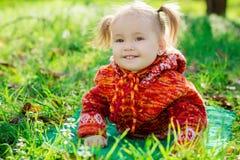 Petite fille se trouvant sur l'herbe en parc image stock