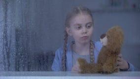 Petite fille seule jouant avec l'ours de nounours à la maison par temps pluvieux, aucun amis banque de vidéos