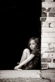 Petite fille seule s'asseyant contre le mur Photographie stock