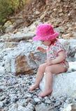 Petite fille seule s'asseyant sur les roches à la plage Photographie stock