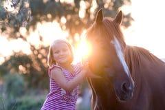 Petite fille smilling mignonne avec son cheval beau Photographie stock libre de droits