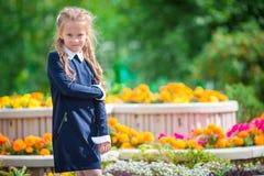 Petite fille smilling mignonne posant devant son école dessus d'abord de septembre Petit enfant adorable se sentant très enthousi Photographie stock libre de droits