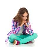 Petite fille songeuse s'asseyant avec des jambes croisées Photo stock