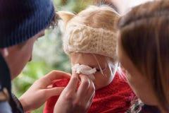 Petite fille soufflant son nez dans le tissu Photo stock