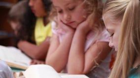 Petite fille souriant à l'appareil-photo pendant le temps de bibliothèque banque de vidéos