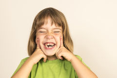 Petite fille souriant avec des yeux fermés Image libre de droits