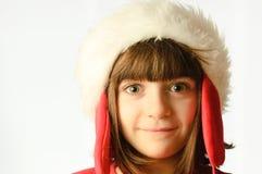 Petite fille souriant avec un chapeau du père noël Photos libres de droits