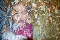Petite fille souriant derrière les rideaux transparents Images libres de droits