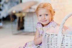 Petite fille souriant, s'asseyant dans sa chambre et regardant l'appareil-photo Photos libres de droits