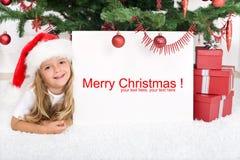 Petite fille sous l'arbre de Noël avec le drapeau Photographie stock libre de droits
