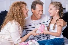 Petite fille stupéfaite obtenant un cadeau d'anniversaire de ses grands-parents Images libres de droits