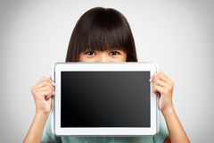 Petite fille supportant une tablette vide obscurcissant le bas photo libre de droits