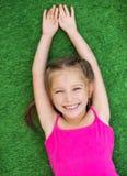 Petite fille sur l'herbe verte photo stock
