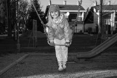 Petite fille sur l'oscillation au terrain de jeu Photographie stock libre de droits