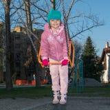 Petite fille sur l'oscillation au terrain de jeu Photo libre de droits