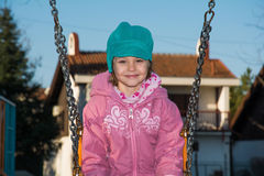 Petite fille sur l'oscillation au terrain de jeu Photo stock